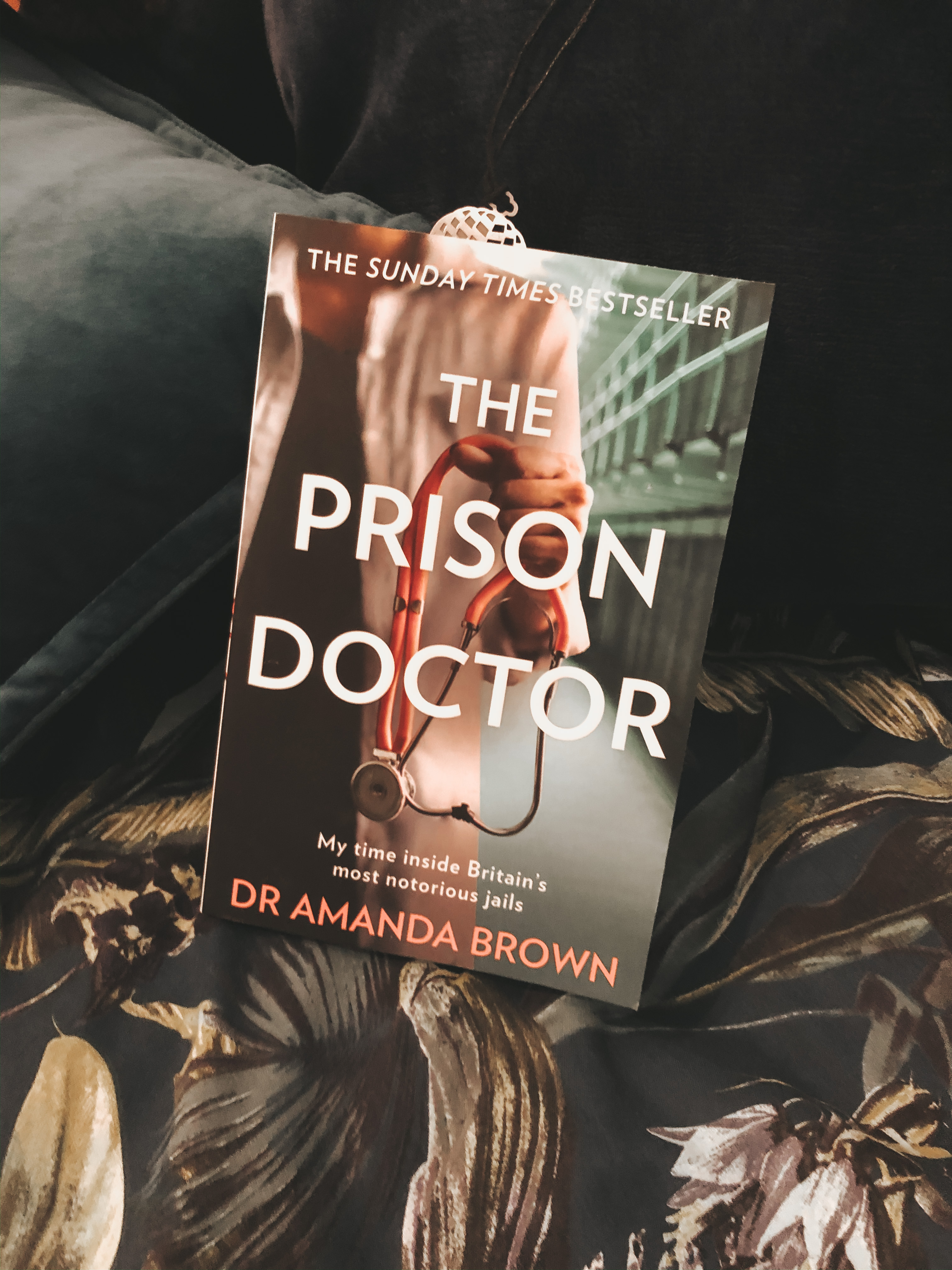 The book 'The Prisn Doctor' propped up with navy cushions