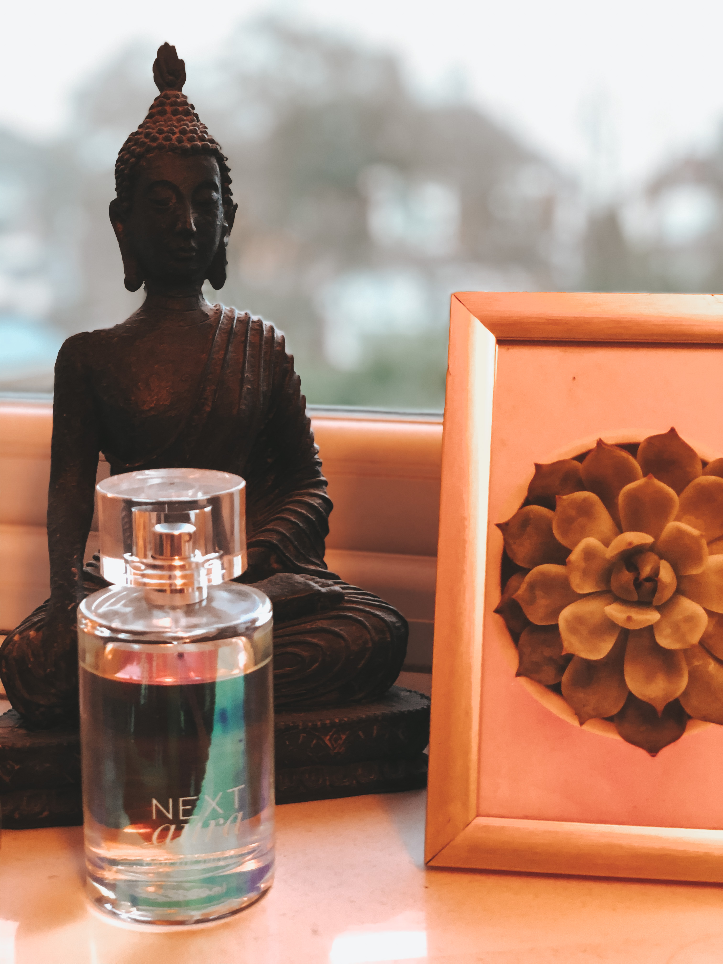 Next Aura perfume on window sill with buddha statue and plant picture frame